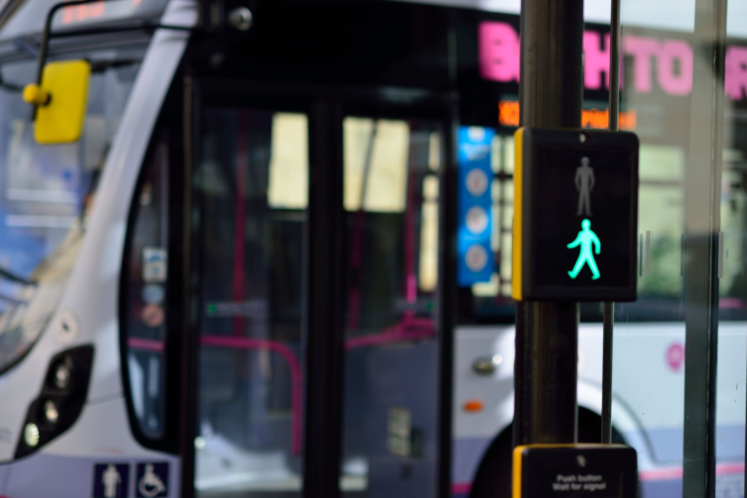 Pedestrian crossing light showing green light, with bus stopped behind it