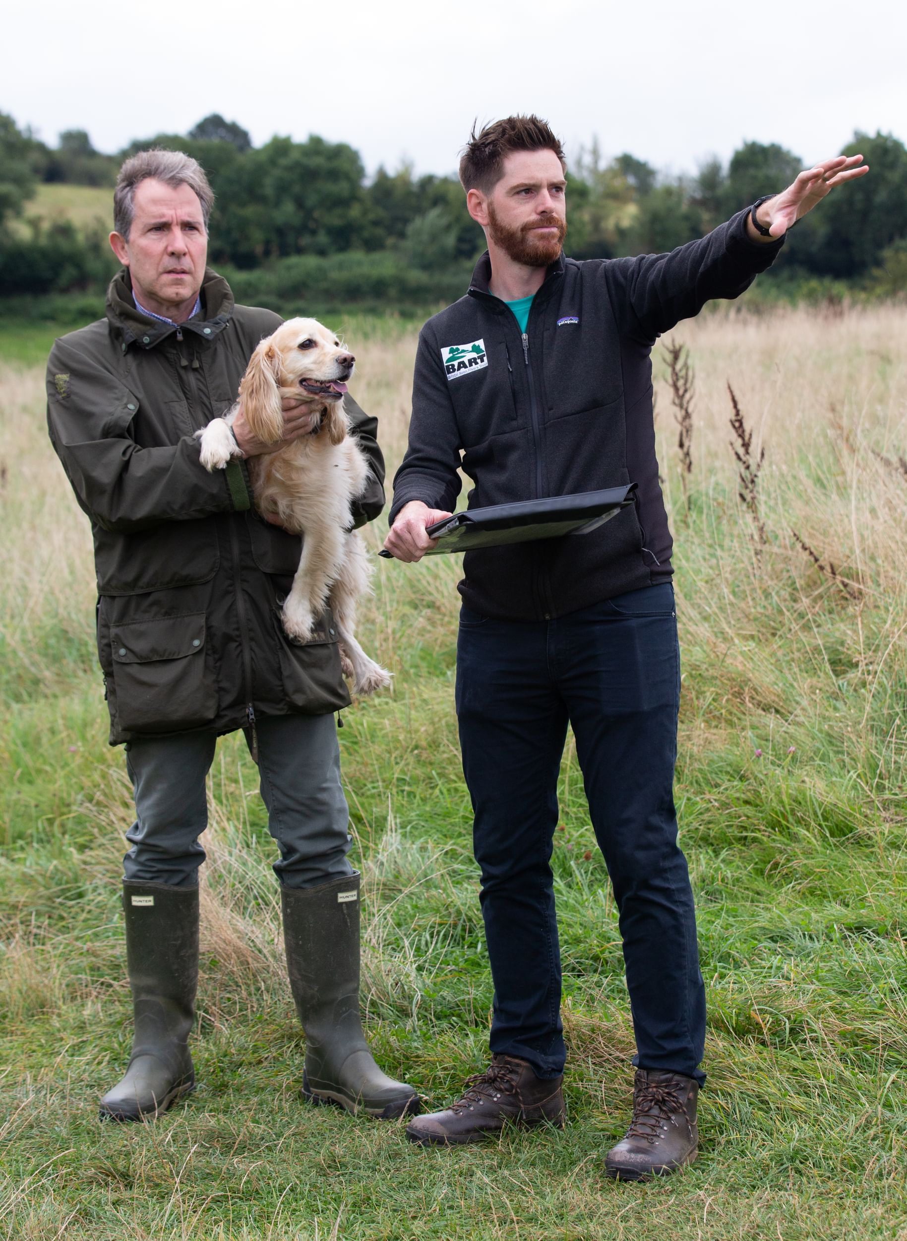 Dan Norris with his dog and a man in a field