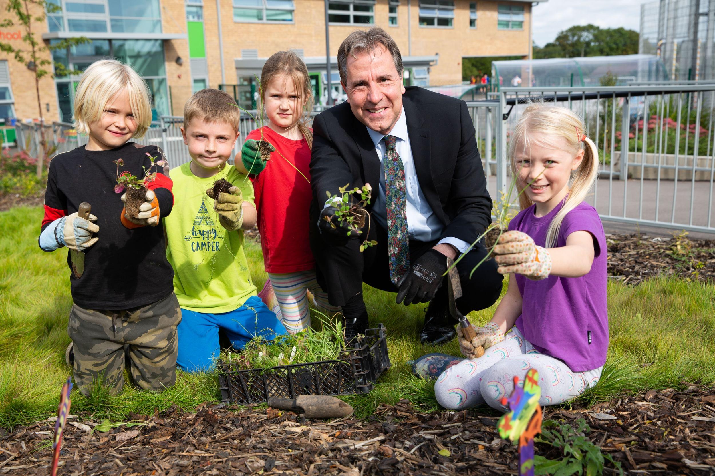 Dan Norris with children doing gardening