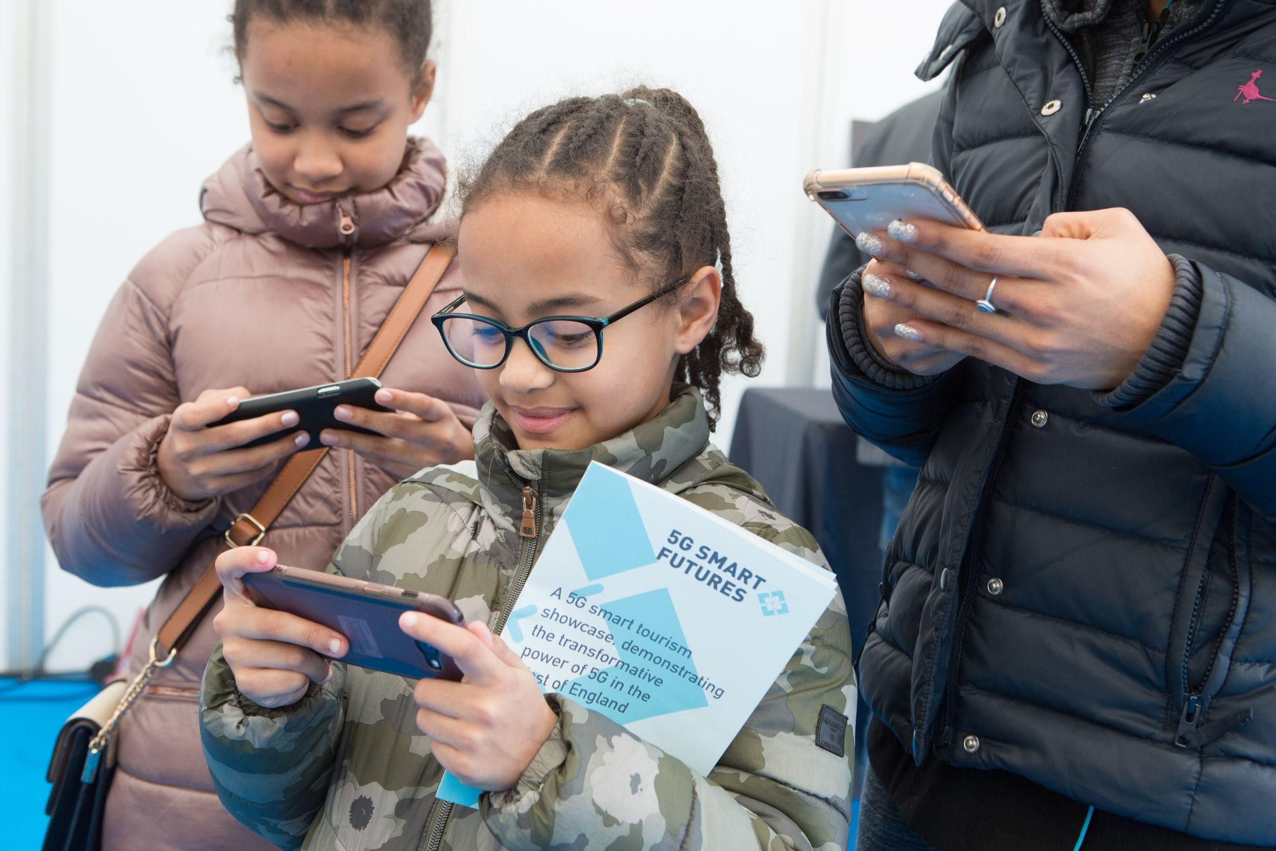 Children looking at 5G smartphones